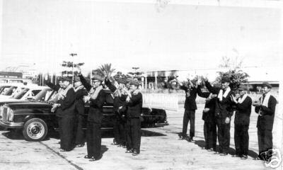 Pol Pot and other Khmer Rouge leaders standing next to Mercedes limousine waiting at Phnom Penh airport to greet arriving VIP delegation