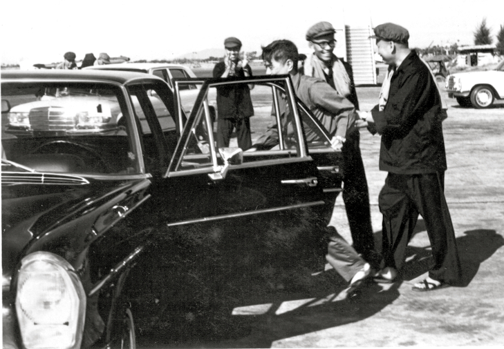 Pol Pot (right) walking into the car. The door was opened by his body guard and he was greeted by Son Sen (second from left), the Khmer Rouge Minister of Defense at Phnom Penh's Pochentong airport in the 1970's