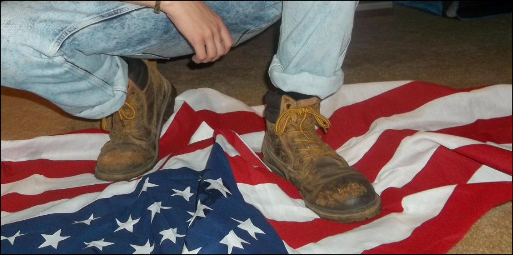Photograph of Dylann Roof taken on May 11 stepping on a U.S. flag. On the middle finger of his right hand is a widely used symbol of the white supremacist movement, the Celtic Cross
