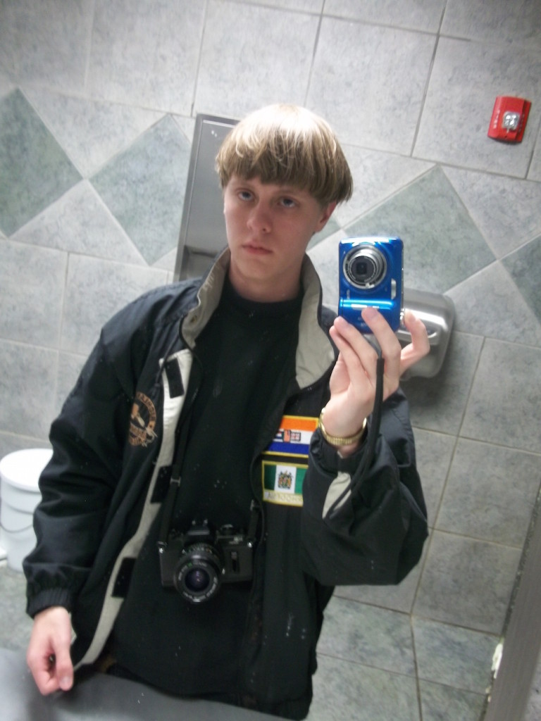 Photo selfie taken by Roof in public restroom. Note him holding one camera and another hanging from strap around his neck