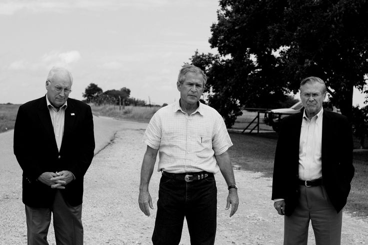 Flanked by U.S. Vice President Dick Cheney and Secretary of Defense Donald Rumsfeld, U.S. President George W. Bush addresses reporters on a road outside his ranch in Crawford, Texas, August 23, 2004. Photo By: Christopher Morris / VII