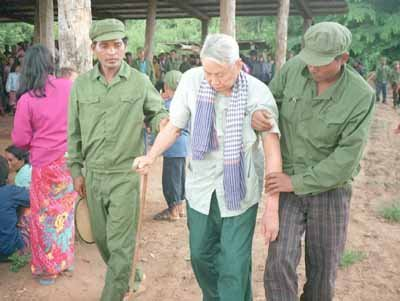 "Notorious Khmer Rouge leader Pol Pot is assisted by soldiers as he arrives to attend his trial 25 July during which he was denounced by former comrades at the Khmer Rouge stronghold of Anlong Veng in northern Cambodia. The veteran revolutionary and three of his top commanders were ""tried"" and sentenced to life imprisonment for the murder of former Khmer Rouge defence minister Son Sen and his family."