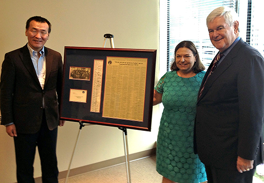 "Newt Gingrich with an elected Mongolian parliamentarian in Washington displaying a framed copy of the ""Contract with Mongolia"""