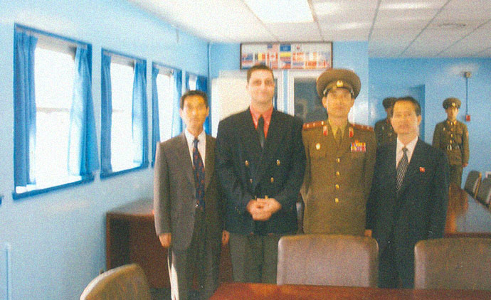 A photograph of John Paul Cupp, Chairman of the U.S Songun Politics Study Group taken at the demilitarized zone on the border with South Korea from the North Korean side. Photo is with a North Korean military officer in the neutral zone during a 2007 trip Cupp made to North Korea as an official guest of Pyongyang