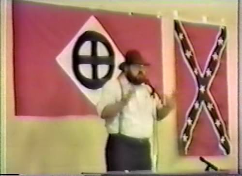 Northwest Front leader Harold Covington, a far right wing neo Nazi White Supremacist who was an ideological source for church shooter Dylann Roof. Note the symbol on the flag behind Covington, which Roof drew in the sand in a photo he posted on his website