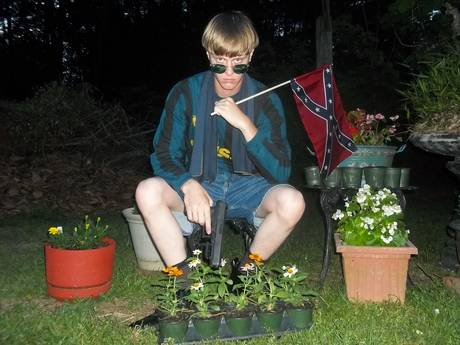 Dylann Roof with Confederate flag and holding the Glock .45 he used to murder 9 God fearing Black people in a South Carolina church June 17