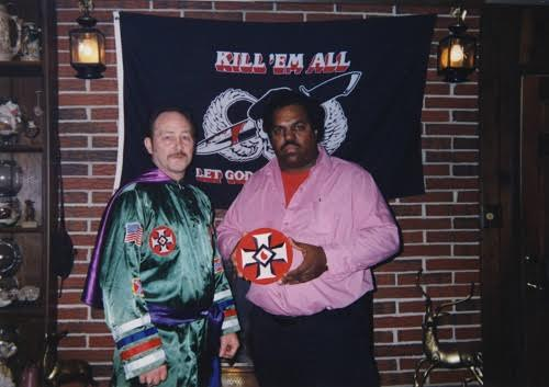 "Davis with KKK leader Robert White. In the background is a banner that reads ""Kill 'Em All"""
