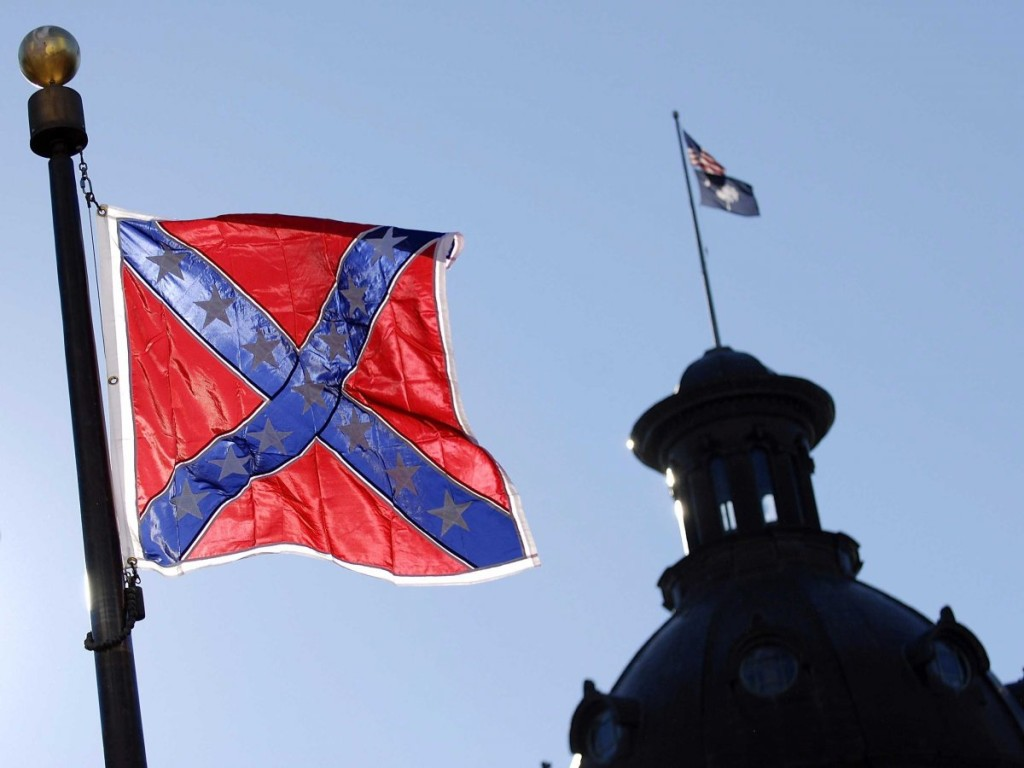 In forefront the Confederate flag flying today at war monument in front of the South Carolina statehouse. In background is the state house dome which is flying the U.S. flag