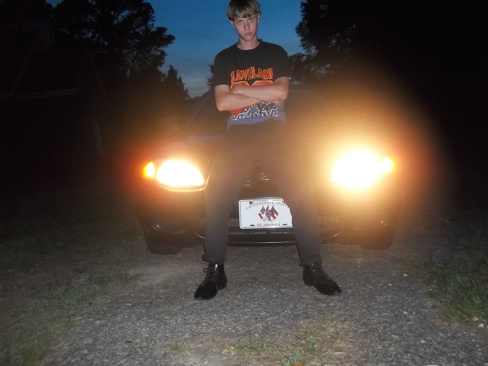 """Photo of Dylann Roof. Note the license plate which depicts the confederate flag and reads """"Confederate States of America"""""""