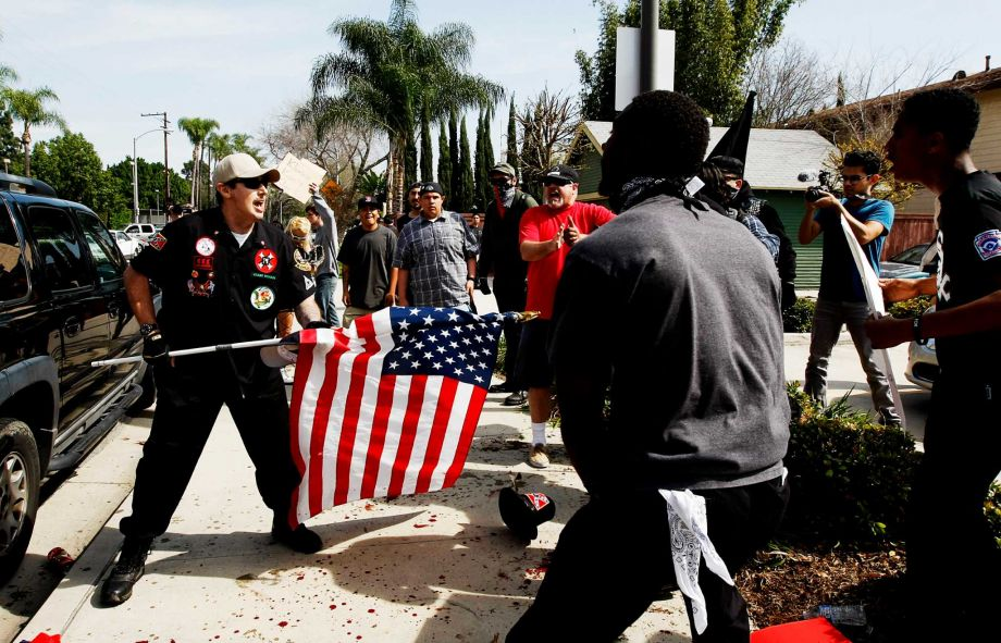"California Loyal White Knights of the KKK state leader William 'Billy Hagen' aka 'Will Quigg"" wielding an American flag during confrontation with counter protestors today in California. The excellent photo taken by LA Times photographer Luis Sinco"
