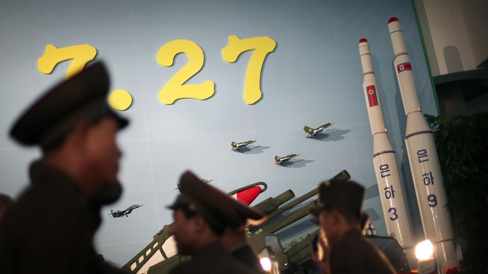 "In this July 26, 2013, photo, North Korean soldiers look at models of the Unha 3 space launch vehicle which successfully delivered North Korea's first satellite into orbit, and on its right, the Unha 9, which would carry a lunar orbiter, on display together with a portrait of late North Korean leader Kim Il Sung, in Pyongyang, North Korea. The Unha 3 rocket that launched the ""Bright Star"" satellite into space in 2012 is a symbol of North Korea's technological successes and a matter of great national pride. (AP Photo/Wong Maye-E)"