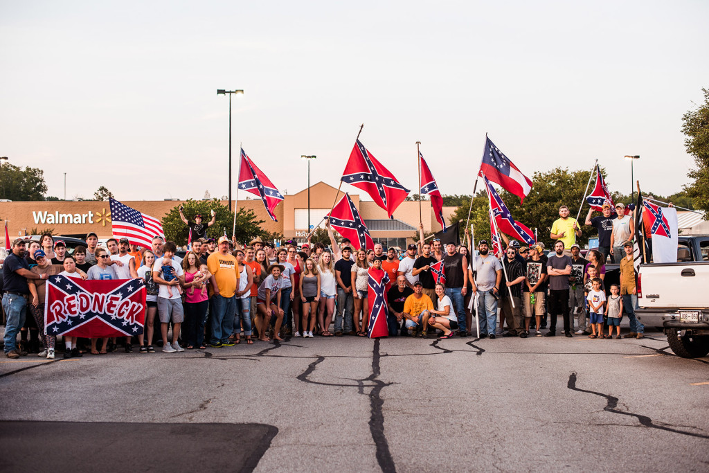 A group gathers for a photo during a confederate flag rally that ended in a parking lot in Knoxville, Tennessee after motorcading through the city on Thursday, July 17, 2015. Host Tom Pierce, and guest, Mathew Heimbach delivered speeches at the meeting place in Seymour, Tennessee before prompting the group to drive through the city with flags raised. Mike Belleme for Al Jazeera America